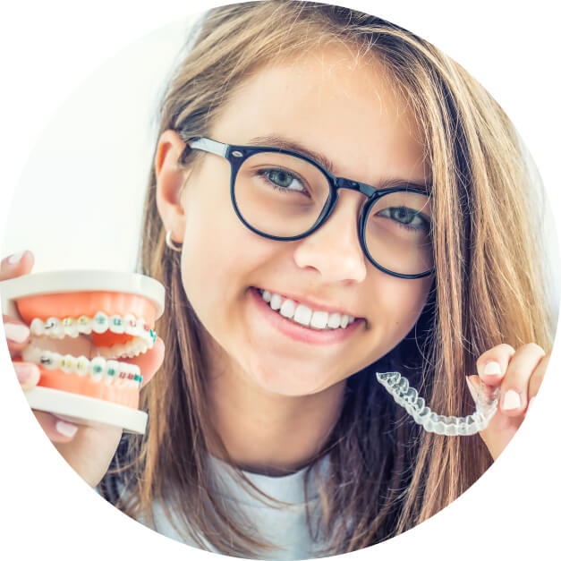 Young female patient holding braces and Invisalign aligners