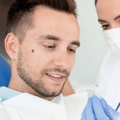 Female staff member showing Invisalign aligners to a young male patient